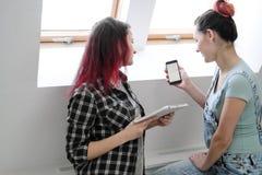Paar van mooie jonge meisjes in een ruimte met witte muren door het venster Communiceer en schrijf op smartphone en royalty-vrije stock afbeeldingen