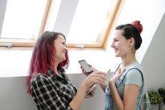 Paar van mooie jonge meisjes in een ruimte met witte muren door het venster Communiceer en schrijf op smartphone en stock afbeeldingen