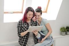 Paar van mooie jonge meisjes in een ruimte met witte muren door het venster Communiceer en schrijf op smartphone en royalty-vrije stock fotografie