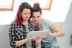 Paar van mooie jonge meisjes in een ruimte met witte muren door het venster Communiceer en schrijf op smartphone en stock afbeelding