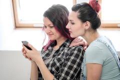 Paar van mooie jonge meisjes in een ruimte met witte muren door het venster Communiceer en schrijf op smartphone en stock foto's