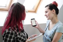 Paar van mooie jonge meisjes in een ruimte met witte muren door het venster Communiceer en schrijf op smartphone en royalty-vrije stock foto's