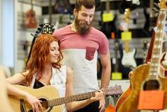 Paar van musici met gitaar bij muziekopslag Stock Foto's