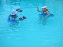 Paar van oudstenoefening in een pool Stock Afbeeldingen