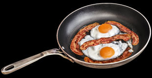 Paar van Sunny Side Up Eggs Fried met Vier Baconplakjes in Oud Op zwaar werk berekend Staal dat Pan Isolated On Black Background  stock foto's