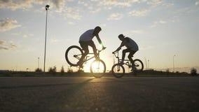 Paar van tienerfietsers die hoogte vijf doen terwijl het uitvoeren van een verbazende voorwheelie op hun fietsen - stock videobeelden