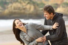 Paar van tienerjaren die en op het strand gekscheren flirten royalty-vrije stock fotografie