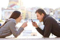 Paar van tienerjaren die hun slimme telefoons op vakantie met behulp van stock fotografie