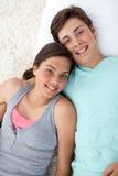Paar van tieners die op de vloer liggen Stock Foto