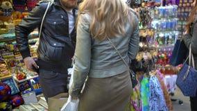 Paar van toeristen die herinneringen bij kleinhandelswinkel, vrouw het plukken toebehoren kopen stock video