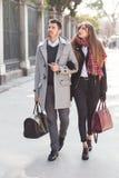 Paar van toeristen die onderaan de straat lopen stock foto
