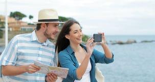 Paar van toeristen die opnamevideo's op het strand lopen