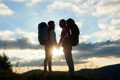 Paar van toeristen in liefde met rugzakken die elkaar onder ogen zien bij zonsondergang in de bergen royalty-vrije stock foto's