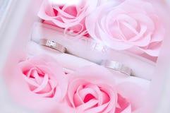 Paar van Twee Ringen in een Doos van Roze Rozen stock fotografie