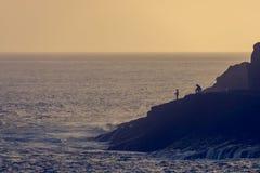Paar van visser visserij van kustlijn bij zonsondergang stock foto