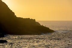 Paar van visser visserij van kustlijn bij zonsondergang stock afbeeldingen