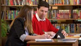 Paar van vrienden betrokken bij de bibliotheek stock video