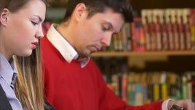 Paar van vrienden betrokken bij de bibliotheek stock footage
