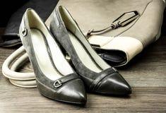 Paar van vrouwelijke die schoenen en handtas op dark worden geïsoleerd royalty-vrije stock foto