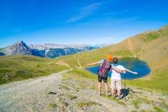 Paar van wandelaar op de bergbovenkant die blauwe meer en bergpieken bekijken De zomeravonturen op de Alpen Brede hoekmening van  Stock Foto
