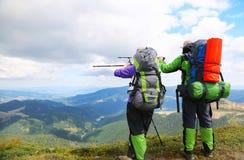 Paar van wandelaars die de manier met trekkingspolen omhoog tonen op p Stock Afbeeldingen