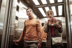 Paar van zakenlieden die de lift nemen terwijl het gaan werken royalty-vrije stock fotografie
