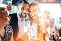 Paar vierende partij in limousine met vrienden royalty-vrije stock afbeelding