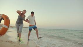 Paar in vinnen lopen onhandig langs de kust stock videobeelden