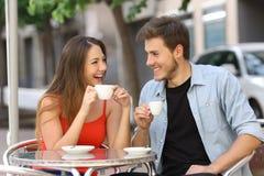 Paar of vrienden die en in een restaurant spreken drinken Stock Afbeelding