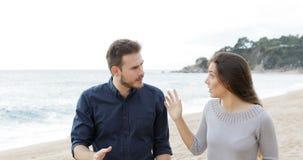 Paar of vrienden die op het strand debatteren stock videobeelden