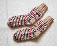Paar warme wollen kleurrijke gebreide sokken op een linnenachtergrond Stock Afbeeldingen