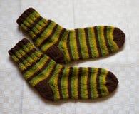 Paar warme wollen kleurrijke gebreide sokken op een linnenachtergrond Stock Foto