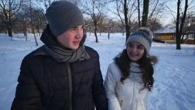 Paar-Winter-Schnee-Forest Walking Young Man And-Frauen-Händchenhalten in Snowy parkt und junge Frau wird beleidigt stock footage