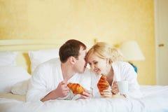 Paar in witte badjassen in bed, die croissants eten stock afbeeldingen