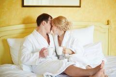 Paar in witte badjassen in bed, het drinken koffie stock foto