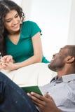 Paar in woonkamer die terwijl het zitten op bank spreken stock foto's