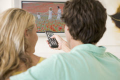 Paar in woonkamer het letten op televisie stock afbeeldingen