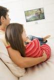 Paar in woonkamer het letten op televisie stock foto