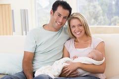 Paar in woonkamer met baby royalty-vrije stock afbeeldingen