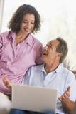 Paar in woonkamer met laptop het glimlachen Stock Foto's