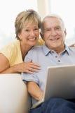 Paar in woonkamer met laptop het glimlachen Royalty-vrije Stock Afbeelding