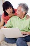 Paar in woonkamer met laptop het glimlachen Stock Foto