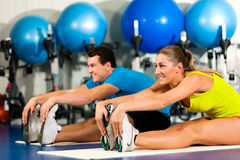 Paar in zich gymnastiek het uitrekken Stock Afbeeldingen