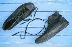 Paar zwarte oude sjofele tennisschoenen met losgemaakt kant royalty-vrije stock foto