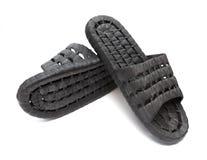 Paar zwarte plastic pantoffels op wit Stock Foto