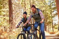 Paarberg het biking door bos, die aan camera kijken royalty-vrije stock afbeelding