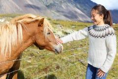 Paard - vrouw die Ijslandse paarden in sweater petting Stock Foto's