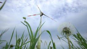 Paardebloemklok en de elektriciteitsgenerator van de windturbine op bewolkte hemel statisch stock footage