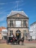 Paardvervoer met koetsier en zijn medewerker voor Waag in Gouda, Nederland Stock Foto's