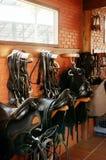 Paardzadels die op rustieke bakstenen muur in warm zonlicht leggen royalty-vrije stock afbeelding